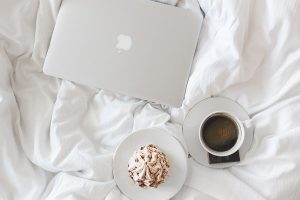 Laptop, coffee and cake on a duvet work from home