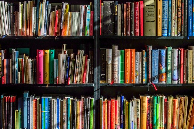 3 bookshelves containing a mix of colours and sizes of book