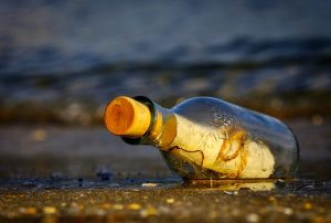 bottle-lying-on-a-beach-with message-inside