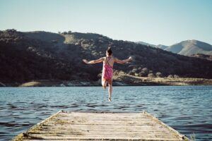 girl-leaping-off-jetty-into-lake